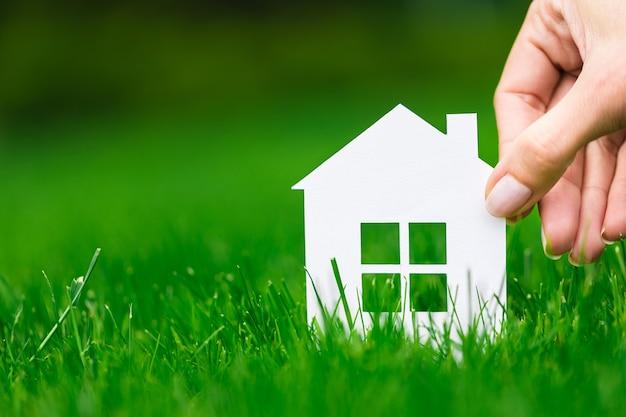 Рука держать дом против зеленого поля