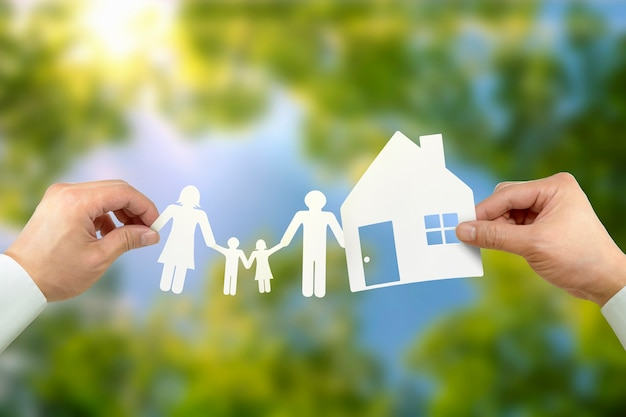 Hand hold house and family on green field