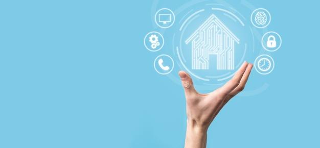 손을 잡고 집 아이콘입니다. 스마트 홈 제어, 지능형 집 및 홈 자동화 앱 개념입니다. pcb 디자인 및 스마트 폰을 사용하는 사람. 혁신 기술 인터넷 네트워크 개념입니다.
