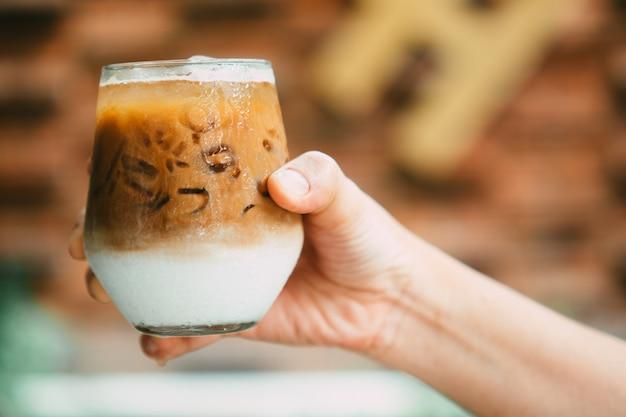 Рука держит замороженный кофе латте в стакане со сливками на дне. холодный летний напиток фон