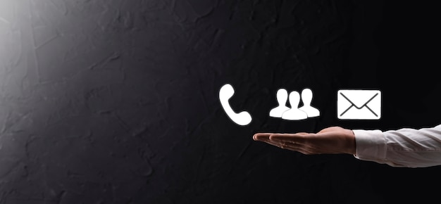 Hand hold icon symbol telephone, email, contact. website page contact us or e-mail marketing concept on dark beton background
