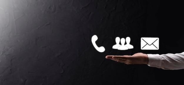 손을 잡고 아이콘 기호 전화, 이메일, 연락처. 웹 사이트 페이지 문의 또는 어두운 beton 배경에 전자 메일 마케팅 개념