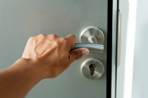 Hand hold on a knob to open the metal door