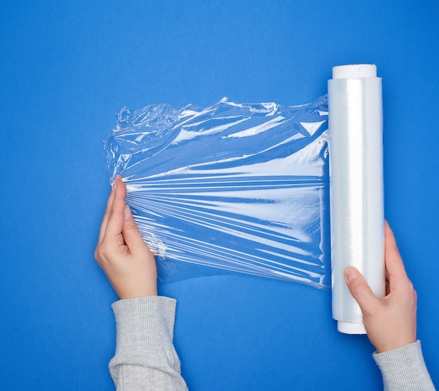 Hand hold a large roll of wound white transparent film for wrapping food
