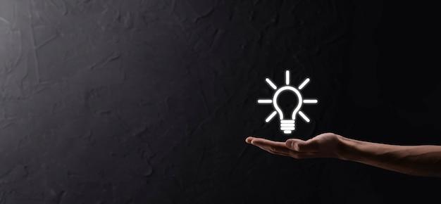 手持ち電球。輝くアイデアのアイコンを手に持っています。テキストの場所があります。ビジネスアイデアの概念。イノベーション、ブレーンストーミング、インスピレーション、ソリューションの概念