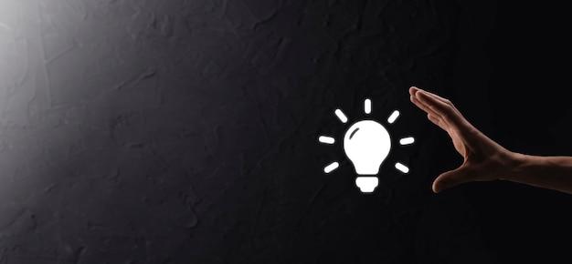 手持ち電球。輝くアイデアのアイコンを手に持っています。テキストの場所があります。ビジネスアイデアの概念。イノベーション、ブレーンストーミング、インスピレーション、ソリューションの概念。