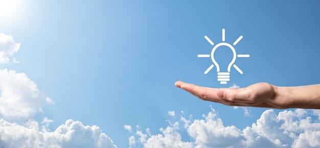 손을 잡고 전구. 그의 손에 빛나는 아이디어 아이콘을 들고 있습니다. 텍스트를위한 장소 비즈니스 아이디어의 개념 혁신, 브레인 스토밍, 영감 및 솔루션 개념