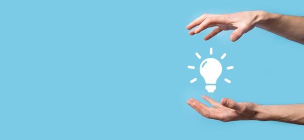 電球を手で持つ。光るアイデア アイコンを手に持っています。テキストのための場所。ビジネス アイデアのコンセプト。イノベーション、ブレーンストーミング、インスピレーション、ソリューションのコンセプト。