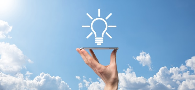 손을 잡고 전구. 손에 빛나는 아이디어 아이콘을 들고 있습니다. 텍스트를위한 장소와 비즈니스 아이디어의 개념 혁신, 브레인 스토밍, 영감 및 솔루션 개념.