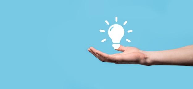 손을 잡고 전구. 그의 손에 빛나는 아이디어 아이콘을 들고 있습니다. 텍스트를위한 장소와 비즈니스 아이디어의 개념 혁신, 브레인 스토밍, 영감 및 솔루션 개념.
