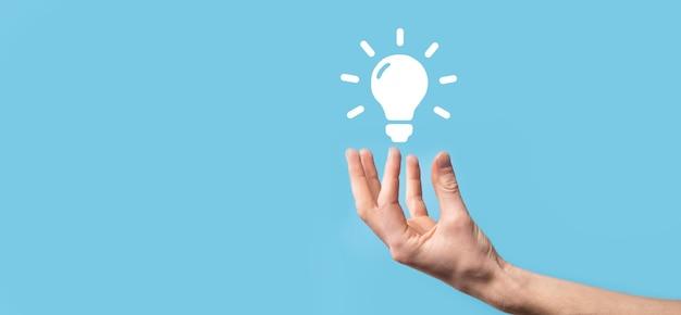 손을 잡고 전구입니다. 그의 손에는 빛나는 아이디어 아이콘이 있습니다. 텍스트를 위한 장소가 있습니다. 비즈니스 아이디어의 개념입니다. 혁신, 브레인스토밍, 영감 및 솔루션 개념입니다.