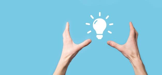 손을 잡고 전구입니다. 그의 손에는 빛나는 아이디어 아이콘이 있습니다. 텍스트를 위한 장소가 있습니다. 비즈니스 아이디어의 개념입니다. 혁신, 브레인스토밍, 영감 및 솔루션 개념