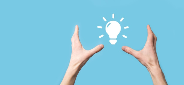 Hand hold light bulb. holds a glowing idea icon in his hand. with a place for text.the concept of the business idea.innovation, brainstorming, inspiration and solution concepts
