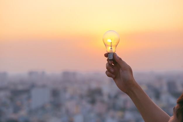 Hand hold a light bulb on sunset background for saving energy and creative concept.