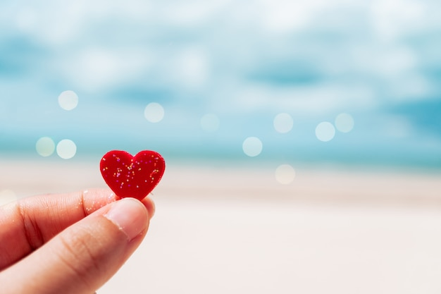 Hand hold little heart meaning feel love with summer beach with blue sky.