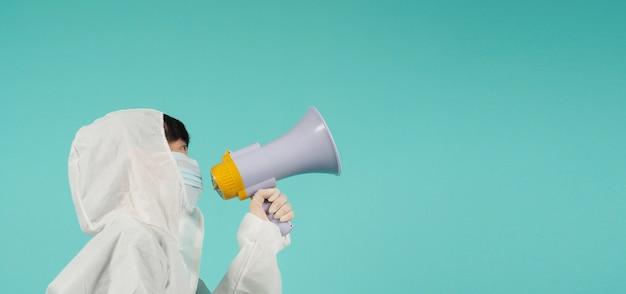 손을 잡고 확성기를 들고 있습니다.아시아 여성은 민트 그린이나 티파니 블루 배경에 얼굴 마스크와 ppe 정장을 입습니다.