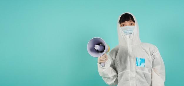 손을 잡고 확성기.아시아 여성은 민트 그린이나 티파니 블루 배경에 ppe 정장과 얼굴 마스크를 착용합니다.