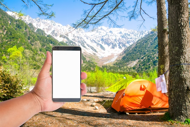 Hand hold mobile phone on tent with a view of japan alps mountain, japan