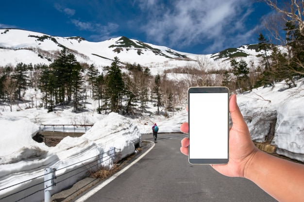 Hand hold mobile phone with a road of snow wall japan alps mountain, japan.