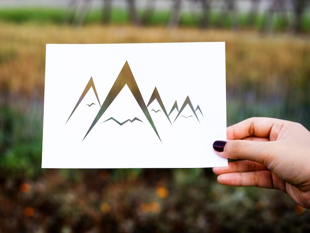 Hand hold mountains paper carving with nature background