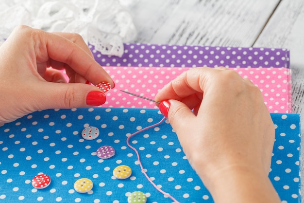 Hand hold needle sew a button