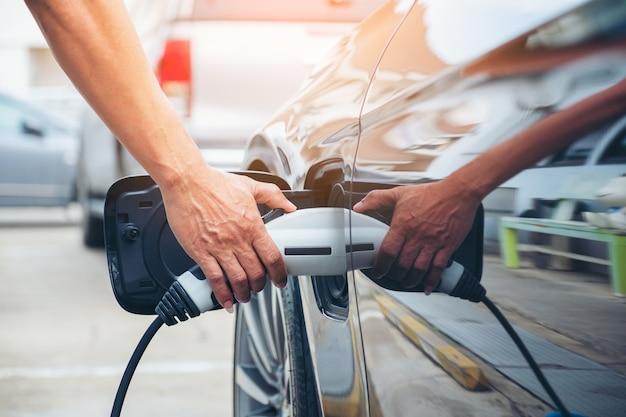 자동차의 미래인 거리에서 현대 전기 자동차 배터리를 충전하는 손 잡기, 하이브리드 자동차를 충전하는 전기 자동차에 연결된 전원 공급 장치의 닫습니다
