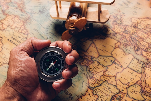 Рука держит старое открытие компаса и деревянный самолет на старинной бумажной антикварной карте мира