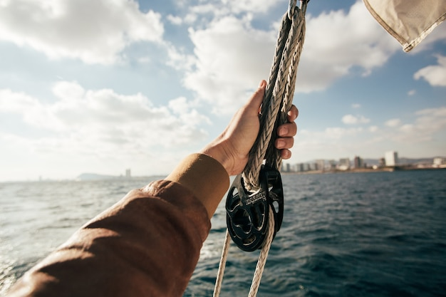 Hand hold onto sail or rope on yacht