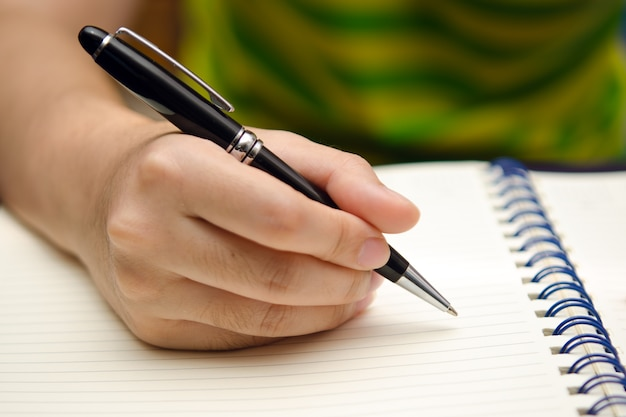 Hand hold a pen and write on a book