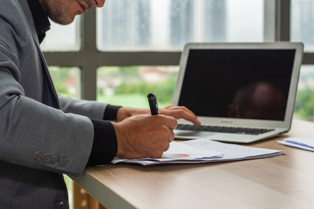 Hand hold pen writing on document, businessman using computer laptop  working technology