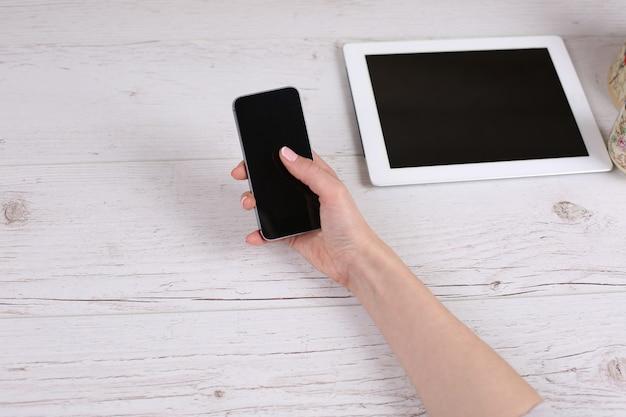 휴대전화를 손에 들고 태블릿이 있는 테이블의 작업 공간을 만집니다.