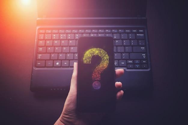 Рука держать телефон с вопросительным знаком виртуальной низкой поли голограммы на фоне ноутбука ноутбука, концепции будущих технологий.