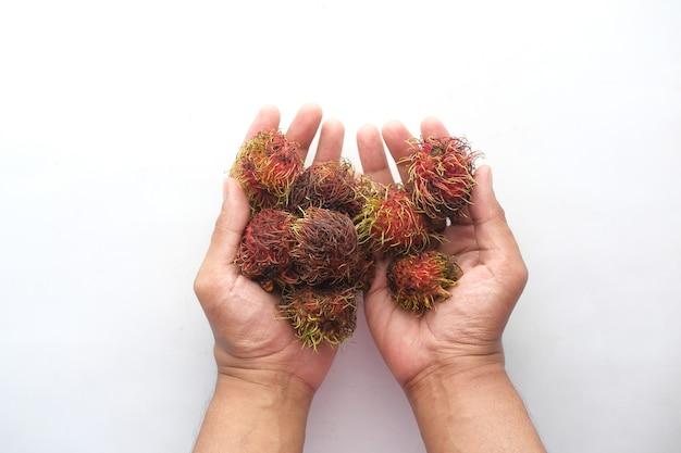 Рука держать фрукты рамбутан на белом фоне