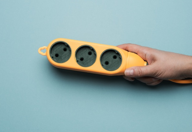 Hand hold rubber orange power strip with three sockets on a blue background, top view