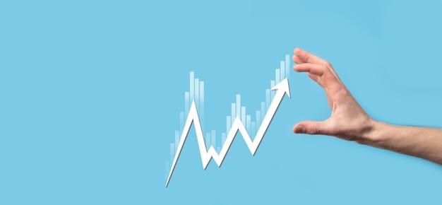 Данные о продажах в руке и диаграмма графика экономического роста. бизнес-планирование и стратегия. анализируем биржевую торговлю. финансово-банковское дело. технологии цифрового маркетинга. план прибыли и роста.
