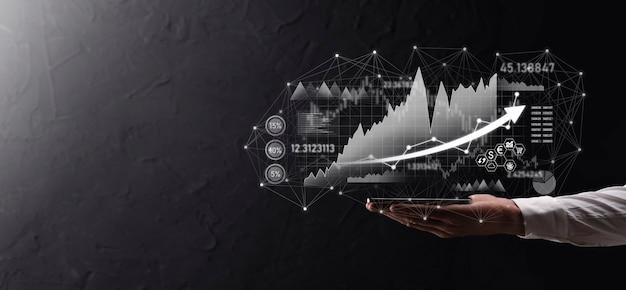 손을 잡고 판매 데이터와 경제 성장 그래프 차트. 사업 계획 및 전략. 교환 거래를 분석합니다. 금융 및 은행. 기술 디지털 마케팅. 이익 및 성장 계획.