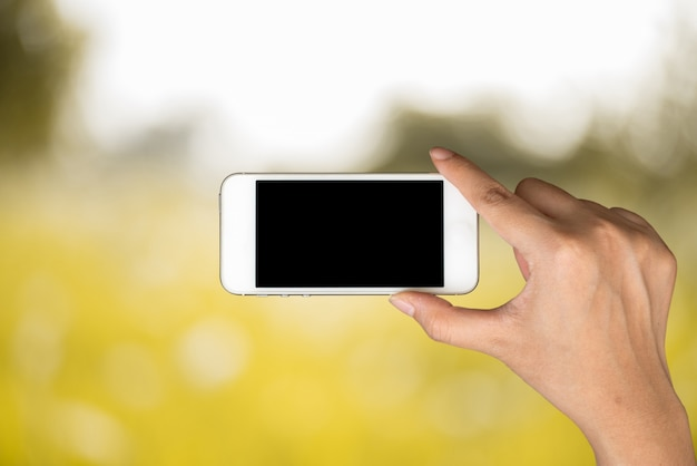 Hand hold and smart phone, tablet,cellphone on day light with yellow blurred nature background.