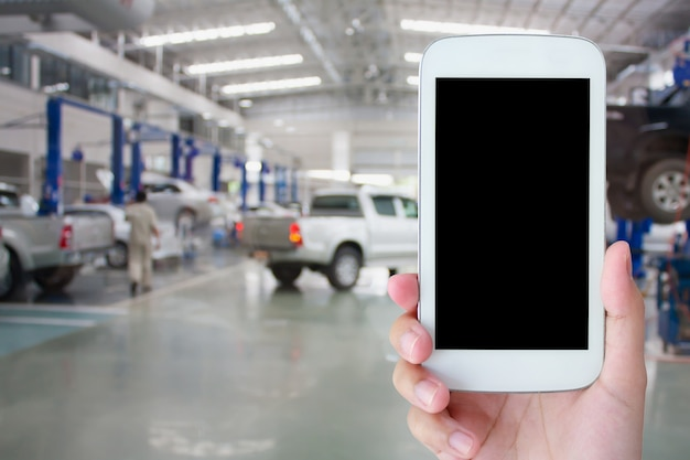 Hand hold smartphone with car repair service center background