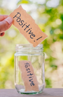 Hand hold think positive message drop jar