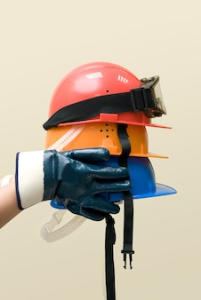 Hand hold three colored helmets