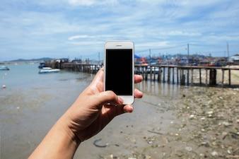 手は美しい新鮮な海とポートで白い携帯電話を持っています。