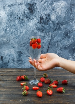 Tenere in mano un bicchiere di vino e fragole in un bicchiere di vino su una superficie di pietra scura. vista laterale.