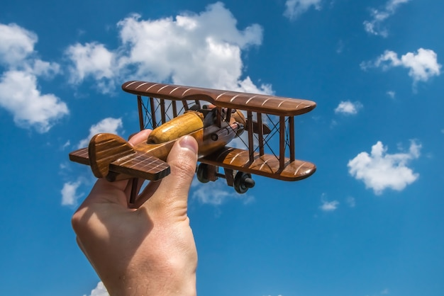 The hand hold a wood plane on the background of the cloud