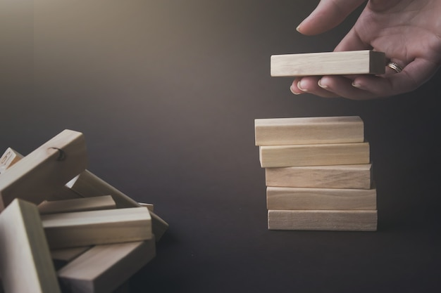Hand hold a wooden block under stack of the same blocks. business conceptual image