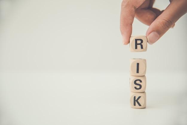 Рука держать деревянный блок со словом «риск». концепция управления рисками