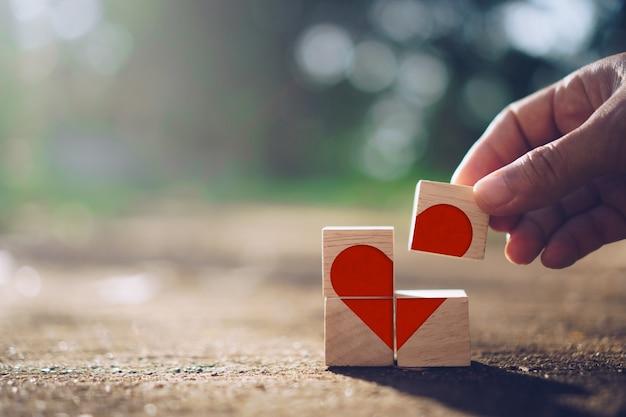 손을 잡고 심장 기호 아이콘으로 나무 큐브 및 복사 공간 자연 햇빛 배경에 텍스트를 넣을 수 있습니다. 발렌타인 데이 사랑 시즌 개념.