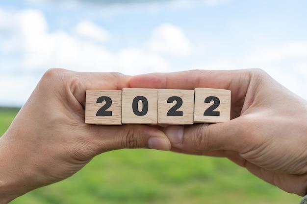 手持ち木製キューブ2022背景、コピースペース。目標の概念、行動計画、戦略、新年またはビジネスビジョン。