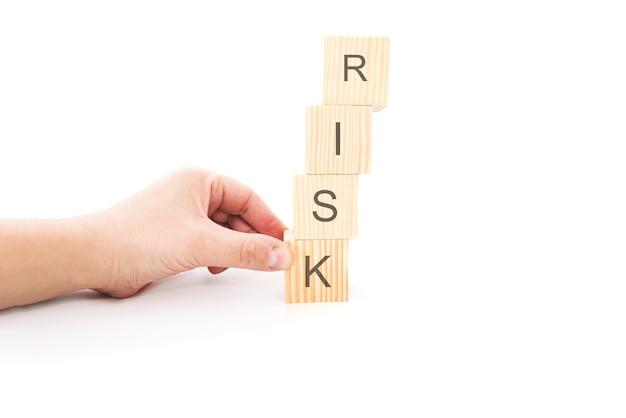 손을 잡고 위험 단어로 나무 큐브. 위험 관리 개념 흰색 배경입니다.