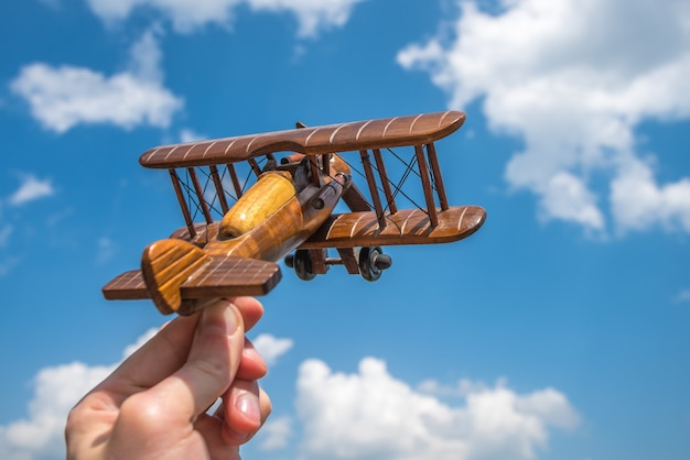 The hand hold a wooden plane on the background of the cloud