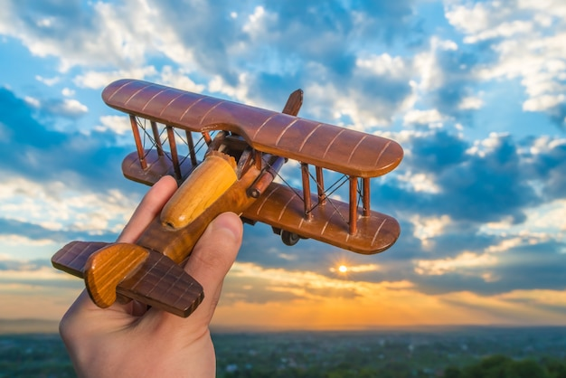 The hand hold wooden plane on the background of a sky